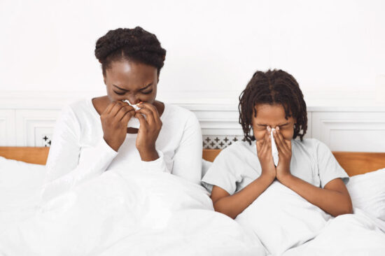 Black girls with allergy symptoms blowing nose